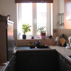 Fertig Sanierte Küche. Doppelflügel Fenster mit Spüle davor. Die Sonne scheint auf die Arbeitsplatte. Küche ist in braun mit heller Arbeitsplatte.