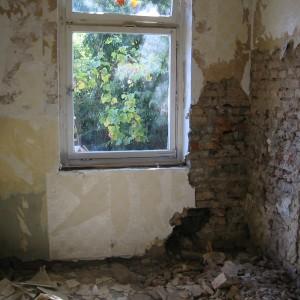 Marode Küche. Bachsteine und Putz fallen ab. Das Fenster mit Blick in den Garten ist versperrt.