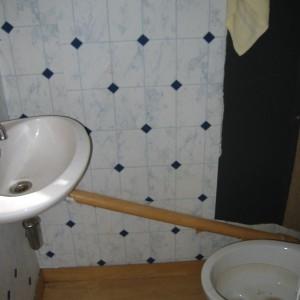 Veraltetes Gäste WC. Installationen müssen entsorgt werden. Fliesenmuster Rechteck in Weiß Blau.