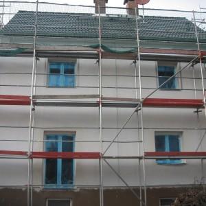 Einfamilienhaus nach Fassadenumbau. Fenster sind abgeklebt und vorbereitet für die Farbe. Gerüst liegt an.