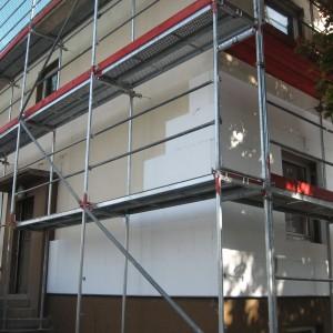 Einfamilienhaus bei der energetischen Sanierung. Gerüst steht aufgebaut im Eingangsbereich.