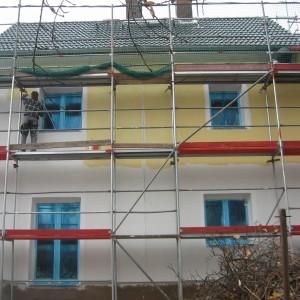 Einfamilienhaus bekommt Fassadenanstrich in gelb mit weissen Laibungen. Handwerker streicht auf dem Gerüst.