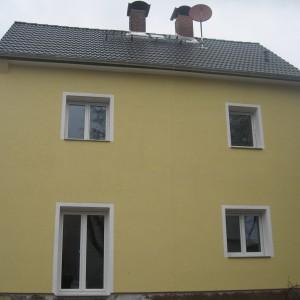 Fertiggestelltes Einfamilienhaus in Gelb weiß mit 3 Fenstern und einer Terrassentür.