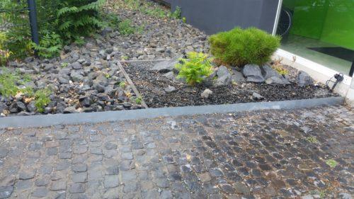 Hofeinfahrt mit Basalt Kopfsteinpflaster. Beete mit Stahlplatten umrahmt. Angelegt ein Steingarten mit Kiefern und Bambus.