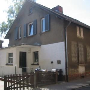Fassadenansicht stark veraltet. Untere Hälfte weiß obere Hälfte braun verfärbt. Eingangsbereich kleine Holzzaun.