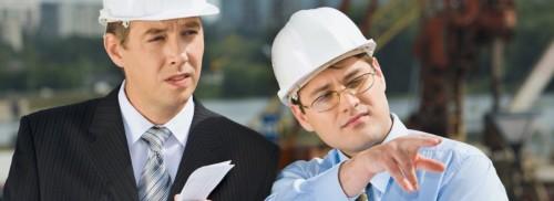 Architekt und Bauherr mit Helmen bei der Bauberatung auf der Baustelle.