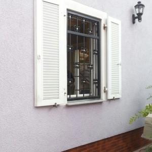 In der Fenster Laibung montiertes Fenstergitter. Weiße Klappläden dienen nur noch als Zierde.