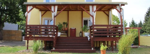 Schwebende Holzterrasse in Bankirai. Gartenansicht. Gelbes Haus mit Bambus und Hofeinfahrt.