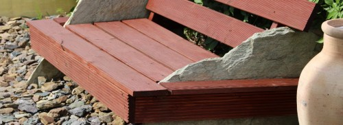 Douglasienholzsitzbank mit Naturstein Polygonalplatten im Steingarten.