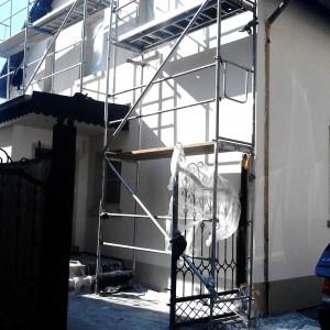 Ansicht Fassaden Sanierung mit WDVS Platten in weiß. Gerüst noch aufgebaut für weitere Arbeiten. Zaun Schmiedeeisernes Tor.