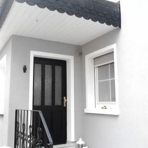 Fertiggestelle Fassadenansicht. Gebäude Grau, Fenter Laibungen weiß. Tür schwarz mit Eisen Geländer.