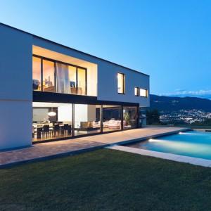 Ansicht vom Garten auf eine Freistehende Villa am Berg. Links das Haus mit Walmdach und Steinterrasse und rechts ein Schwimmbad. Mit Blick in das Tal.