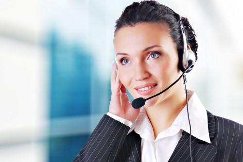 Frau mit Headset ist am telefonieren. Ihre rechte Hand hält sie sich an ihr Ohr.