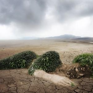 Eine aus Sand geformte Frau in der Wüste. Seitlich liegend. Linke sichtbare Seite mit Gräsern verziert. Klimawandel.