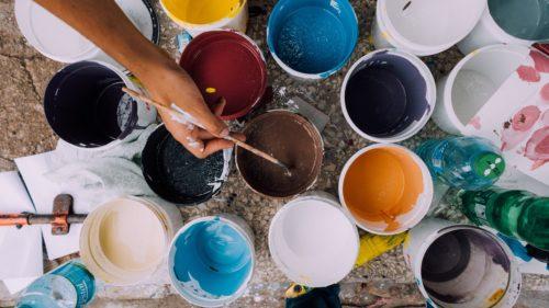 Verschiedene Farbdosen auf dem Boden. Eine Hand mit Pinsel die in braun tunkt. Blau Gelb Rot Blau Orange in kleinen Farbeimern.