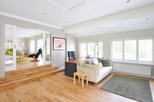 Wohnzimmer mit angrenzendem Büro. Weiße Decken mit hellem Eichen Parkett Boden im Splittlevel Bau.